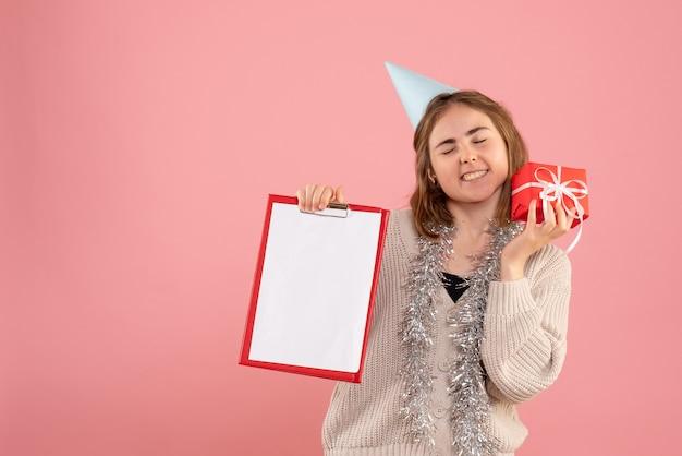 Jonge vrouw met kleine kerst aanwezig en nota over roze