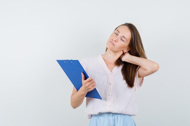 Jonge vrouw met klembord met hand op nek in t-shirt, rok en op zoek moe, vooraanzicht.