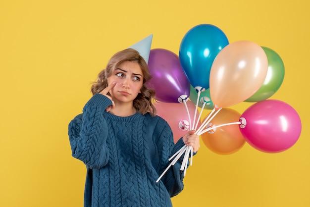 Jonge vrouw met kleurrijke ballonnen achter haar rug op geel
