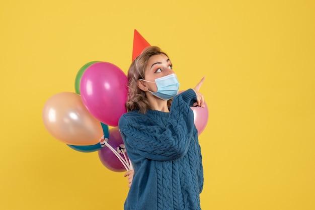 Jonge vrouw met kleurrijke ballonnen in masker op geel