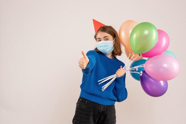 Jonge vrouw met kleurrijke ballonnen in masker op wit