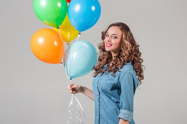 Jonge vrouw met kleurrijke ballonnen op grijze studiomuur