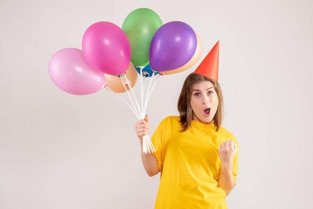 Jonge vrouw met kleurrijke ballonnen op wit