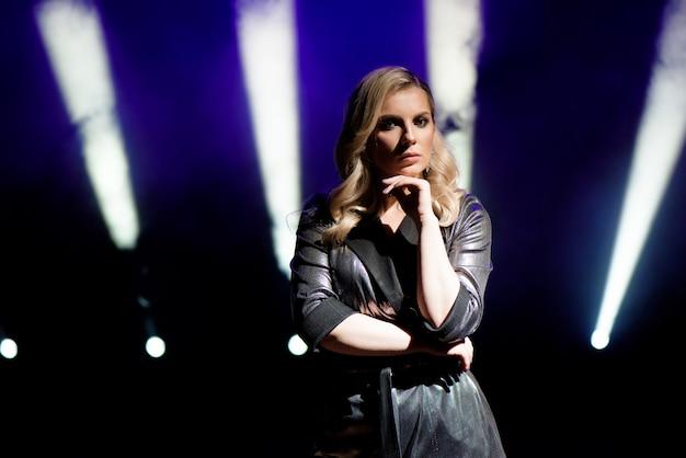 Jonge vrouw met kleurrijke lichten op concert op het podium