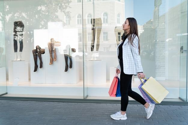 Jonge vrouw met kleurrijke pakjes loopt langs etalages. winkelverslaafd.