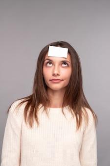Jonge vrouw met kleverig document op voorhoofd