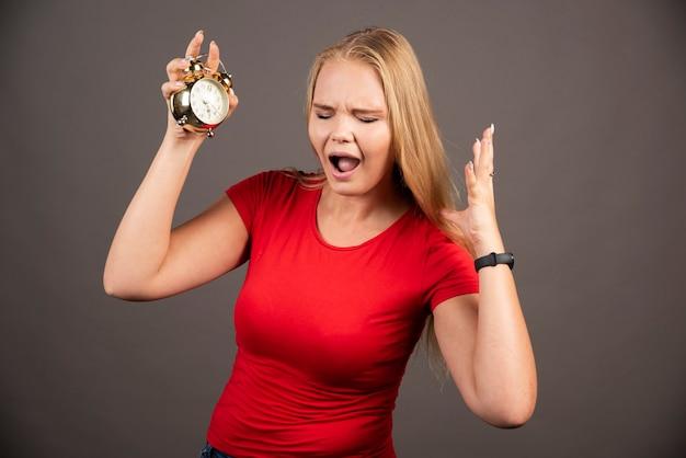Jonge vrouw met klok die analyse heeft.