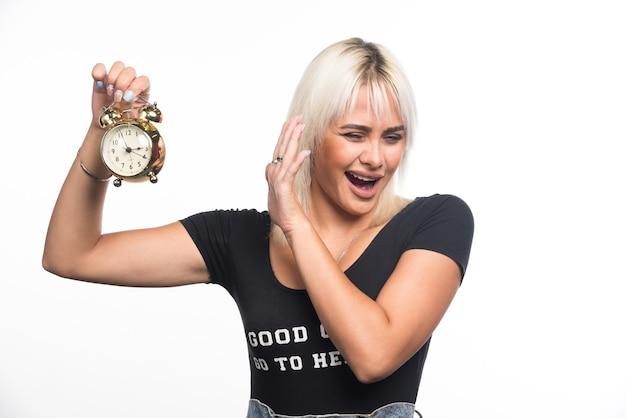 Jonge vrouw met klok terwijl ze haar hand erop richt op een witte muur.