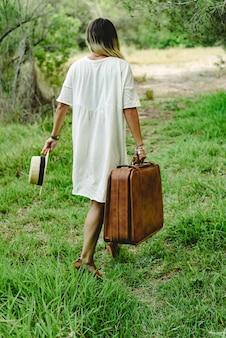Jonge vrouw met koffer en strohoed in het alleen en droevige hout lopen.