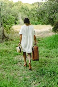 Jonge vrouw met koffer en strohoed in het alleen en droevige hout lopen. Premium Foto