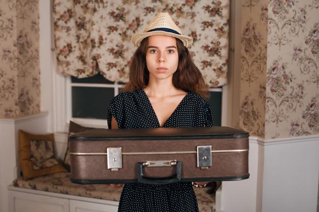 Jonge vrouw met koffer in haar handen.