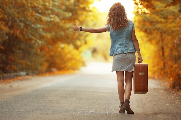 Jonge vrouw met koffer liftend op de weg