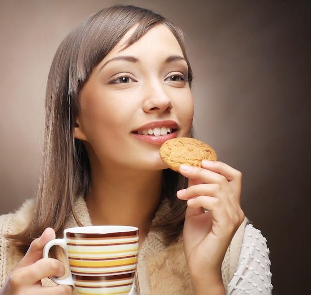 Jonge vrouw met koffie en koekjes.