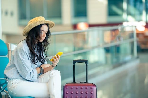 Jonge vrouw met koffie in een luchthavenzitkamer die op vluchtvliegtuigen wacht