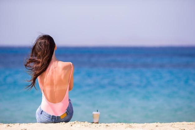 Jonge vrouw met koffie op het strand tijdens tropische vakantie. meisje geniet van haar wekeend op een van de prachtige stranden in mykonos, griekenland, europa.