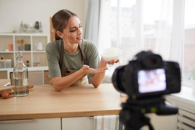 Jonge vrouw met kom in haar hand en praat over het recept in de binnenlandse keuken