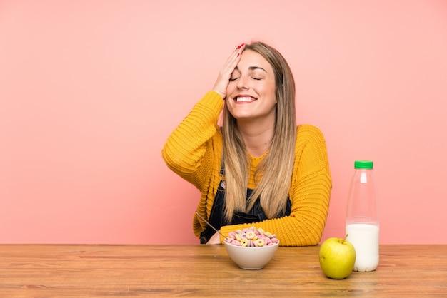 Jonge vrouw met kom ontbijtgranen lachen