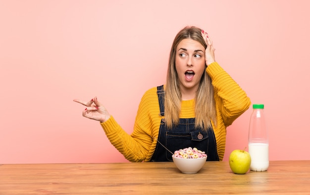Jonge vrouw met kom verrast ontbijtgranen en wijzende vinger aan de zijkant