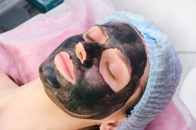 Jonge vrouw met koolstof nanogel op haar gezicht in salon. schilprocedure.