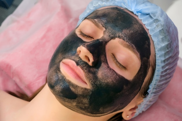 Jonge vrouw met koolstofnanogel op haar gezicht in salon. schilprocedure.