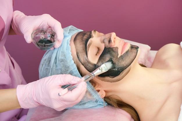 Jonge vrouw met koolstofnanogel op haar gezicht in salon