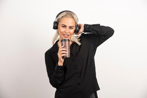 Jonge vrouw met kop in hoofdtelefoons op een rode muur.