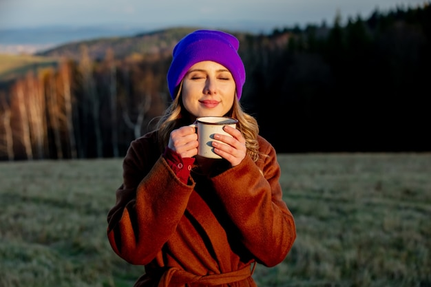Jonge vrouw met kopje koffie blijft in de buurt van hout in zonsondergangtijd