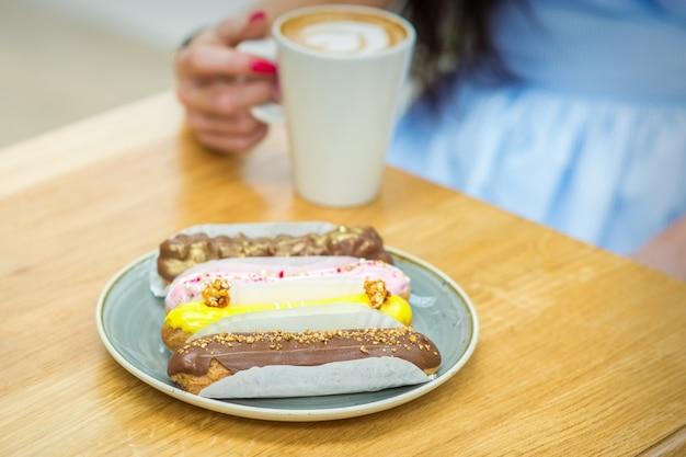 Jonge vrouw met kopje koffie en fluitje van een cent zittend aan de tafel in een café buitenshuis