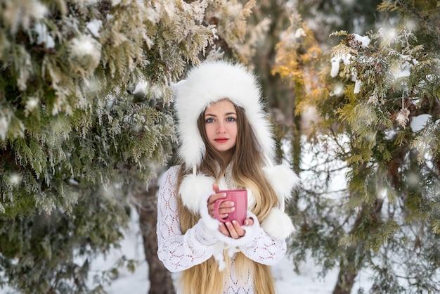 Jonge vrouw met kopje koffie in winter park