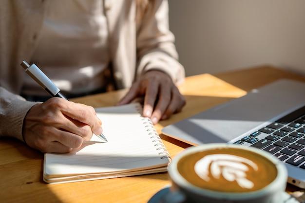 Jonge vrouw met kopje koffie zitten en werken op laptop bij coffeeshop