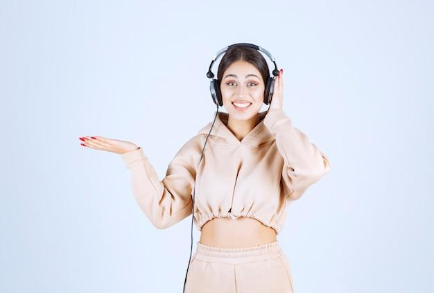 Jonge vrouw met koptelefoon die iemand aan de linkerkant wijst of opmerkt