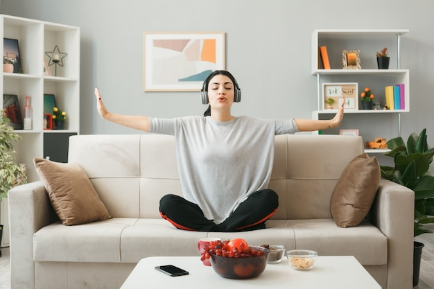 Jonge vrouw met koptelefoon die yoga doet, zittend op de bank achter de salontafel in de woonkamer