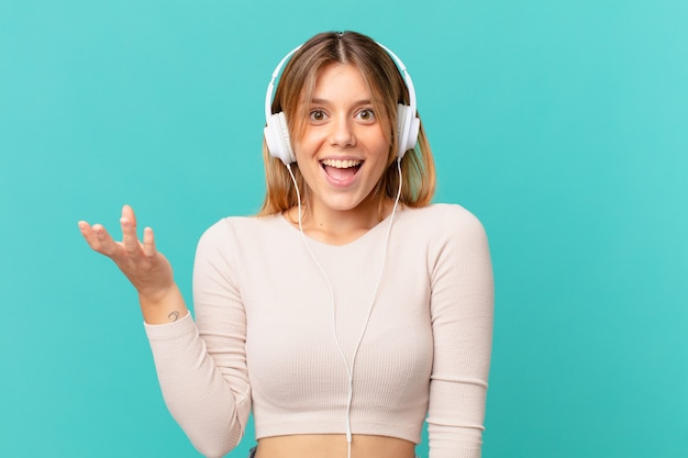 Jonge vrouw met koptelefoon die zich gelukkig, verrast voelt bij het realiseren van een oplossing of idee