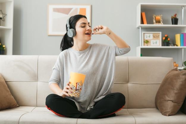 Jonge vrouw met koptelefoon eet popcorn zittend op de bank achter de salontafel in de woonkamer