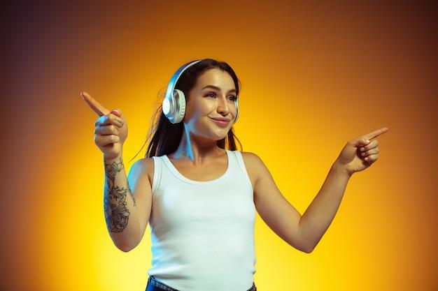 Jonge vrouw met koptelefoon geïsoleerd op gele wall
