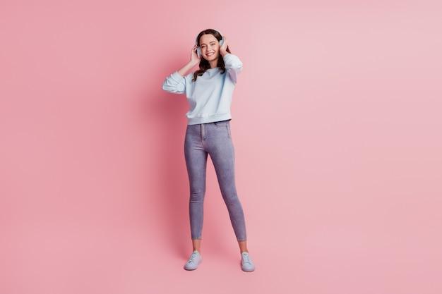 Jonge vrouw met koptelefoon luisteren muziek dans veel plezier op roze achtergrond
