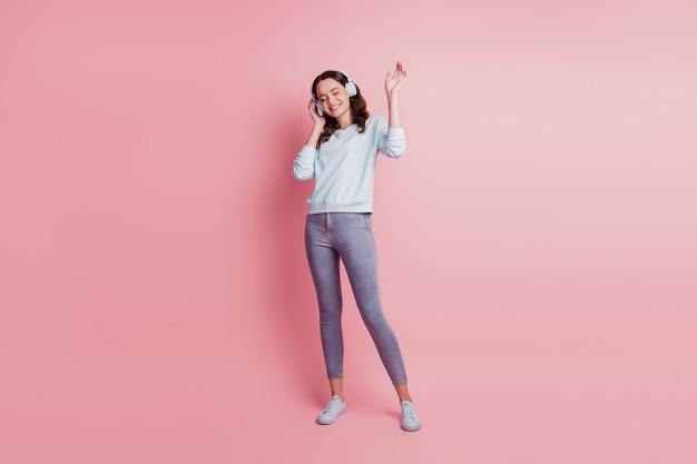 Jonge vrouw met koptelefoon luisteren muziek geniet van feest op roze achtergrond