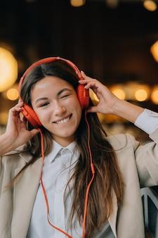 Jonge vrouw met koptelefoon luistert naar muziek terwijl ze in cafés zit