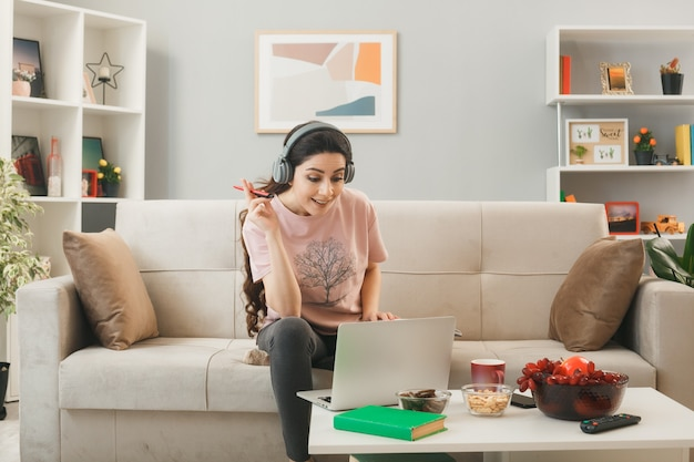 Jonge vrouw met koptelefoon met pen gebruikte laptop zittend op de bank achter de salontafel in de woonkamer