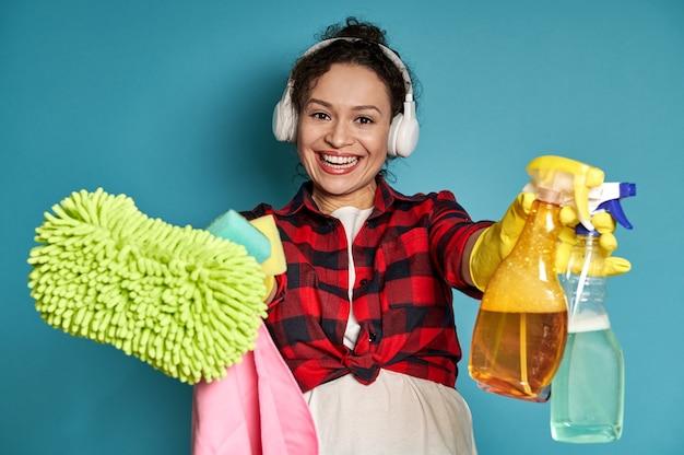 Jonge vrouw met koptelefoon strekt zich uit en toont aan de camera een doek voor het reinigen van het oppervlak en een spray met afwasmiddel