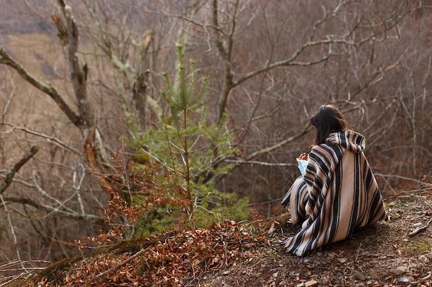 Jonge vrouw met kort donkerbruin haar in poncho zetel neer in de herfstbossen, bos.