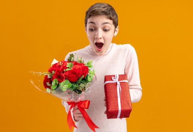 Jonge vrouw met kort haar bedrijf boeket van rode rozen en een cadeautje op zoek verbaasd en verrast valentijnsdag concept staande over oranje muur