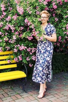 Jonge vrouw met kort haar dichtbij een bloemstruik