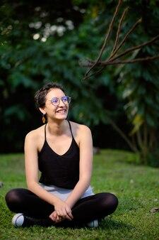 Jonge vrouw met kort haar en glazen zittend op een groene weide en glimlachend omhoog kijken naar de hemel.