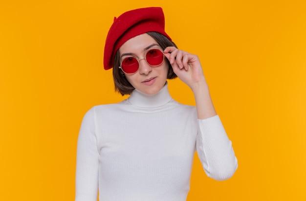 Jonge vrouw met kort haar in een witte coltrui die een baret en een rode zonnebril draagt en naar de voorkant kijkt glimlachend zelfverzekerd blij en positief staande over oranje muur