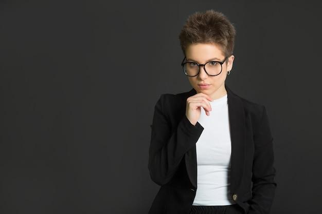 Jonge vrouw met kort haar, in een zwart pak en een bril op een zwarte muur