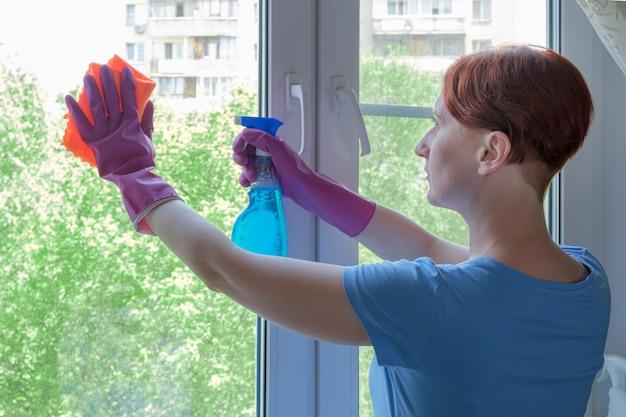 Jonge vrouw met kort haar in rubberen handschoenen wast raam in haar appartement met vod
