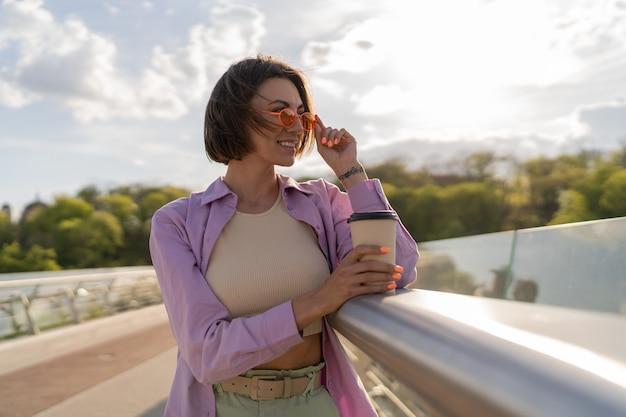 Jonge vrouw met kort haar in stijlvolle zomeroutfit drinkt koffie op thr moderne brug