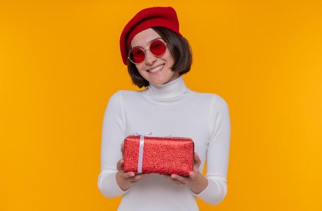 Jonge vrouw met kort haar in witte coltrui die baret en rode zonnebril draagt die een heden gelukkig en positief houdt