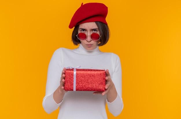 Jonge vrouw met kort haar in witte coltrui met baret en rode zonnebril met een cadeau naar voren kijkend met fronsend gezicht beledigd staande over oranje muur